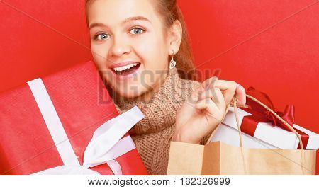 Young woman is standing while holding a bag of gifts over her shoulder