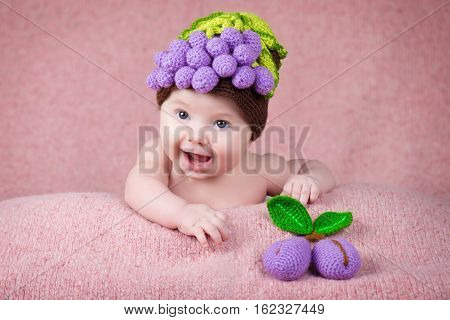 Newborn baby in a knitted cap in the form of grapes.