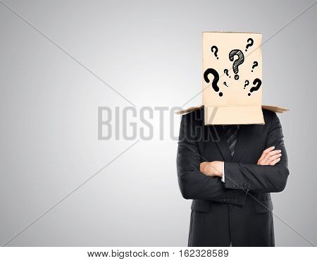 Businessman with folded arms and cardboard box with question marks covering head on grey background. Confusion concept