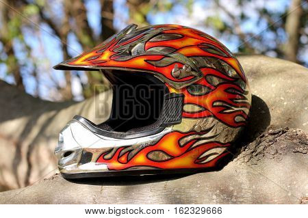 Flame painted bike racing helmet sitting on a tree branch on a sunny day.