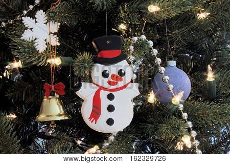 Hand painted snowman ornament hanging in a Christmas tree.
