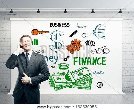 Successful businessman talking on phone in modern brick interior with creative money sketch. Success and wealth concept