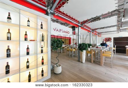 """MOSCOW - AUGUST 2014: Interior of the international chain Italian restaurant home cuisine """"Vapiano"""". Rack with bottles of wine at the entrance"""