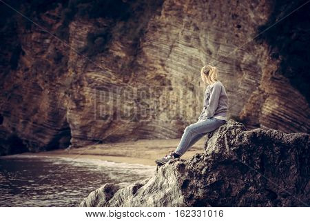 Pensive lonely young woman traveler relaxing on a big cliff stone on the beach looking at wild mountain scenery in retro vintage style