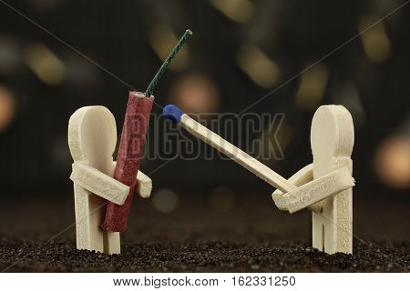 One small wooden male holds a banger and the other one holds a matchstick