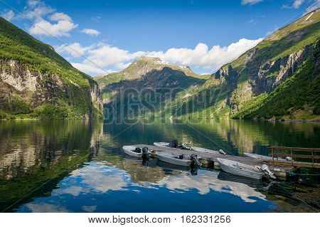 Scenic norwegian fjord landscape with fishing boat's pier. Beautiful morning sun light and mirror reflections on the water. Geiranger fjord, Norway.