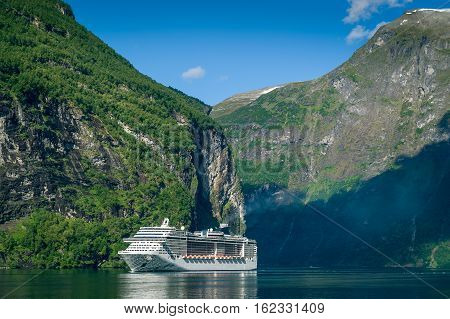 Big white ferry ship at the steep rocky shores of Geiranger fjord, Norway.
