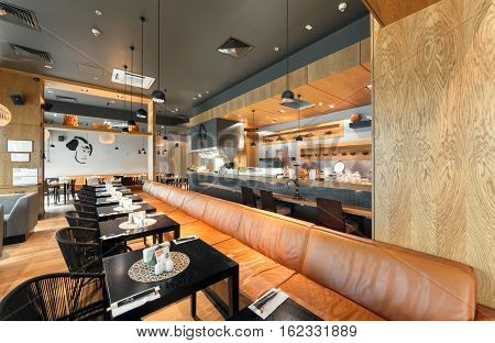 """MOSCOW - AUGUST 2014: Interior of a Japanese restaurant bar and lounge """"KABUKI"""" The main hall with a open kitchen and a long leather sofa along the tables"""