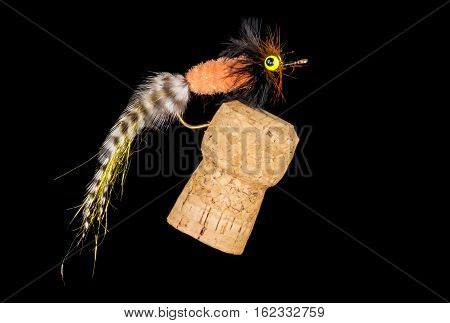 Colorful Hand Tied Fishing Fly Displayed on Champagne Cork Isolated on Black