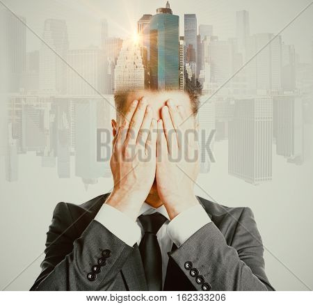 Man covering face with hands on abstract city background with sunlight. Double exposure. Future concept