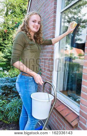 Young caucasian woman washing home window outdoors