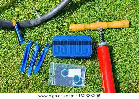 Flat tire of bicycle with repair material outdoors on grass