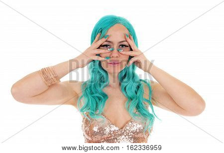 A young pretty woman with long blue hair and blue fingernails holding her fingers over her face isolated for white background.