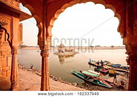 JAISALMER, INDIA - FEB 2, 2015: Wooden riverboats on river with ancient indian arches of old buildings on February 2, 2015. Every winter Jaisalmer takes famous Desert Festival of Rajasthan