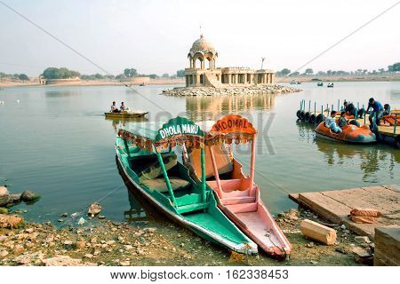 JAISALMER, INDIA - FEB 2, 2015: Colorful riverboats on river with relaxing tourists on February 2, 2015. Every winter Jaisalmer takes famous Desert Festival of Rajasthan