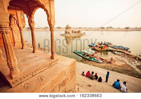JAISALMER, INDIA - FEB 2, 2015: Colorful boats on indian river and group of tourists having rest near water on February 2, 2015. Every winter Jaisalmer takes famous Desert Festival of Rajasthan