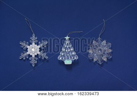 Christmas \ New year toys on a dark blue background. Decoration in the form of snowflake and herringbone. Top view, flat lay