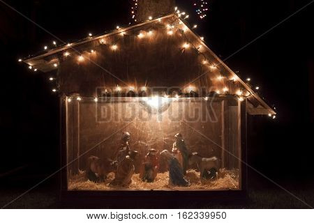 Christmas Nativity scene depicting the birth of Jesus Christ decorated with lights at night.