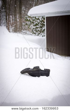 A pair of worn out boots sunken in a big mound of snow, concept of being stressed out for the holidays.