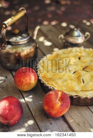 Delicious homemade peach pie with fresh fruits peaches and vintage kettle on old wooden table outdoors. Selective focus. Eating concept.
