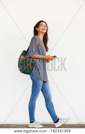 Happy Young Woman Walking Outside With Mobile Phone
