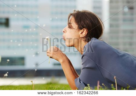 Young Woman Lying On Grass And Blowing Dandelion