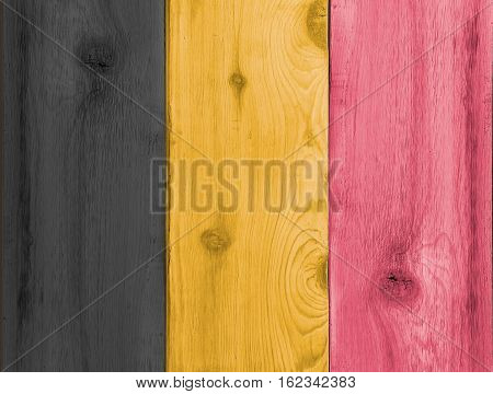 Timber planks of wood that have been painted or stained in the colors of a Belgium flag as a background