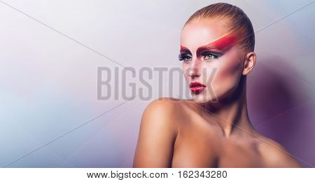 Beautiful woman with fashion make-up in the studio on a light background
