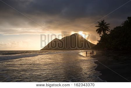 Martinique the picturesque Le Diamant beach at sunset. Caribbean palms on the beach at sunset in West Indies