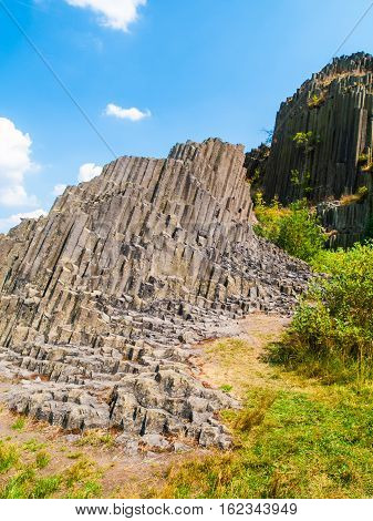 Unique basalt organ pipes rock formation of Panska skala near Kamenicky Senov in Northern Bohemia, Czech Republic, Europe. Shot on sunny summer day with blue sky and white clouds.