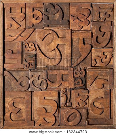Old wooden letterpress blocks for Indian language. Collage made with various Hindi letter characters.