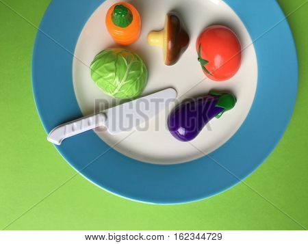 Set of plastic miniature vegetable models in a plate. Kid education with fun toys.