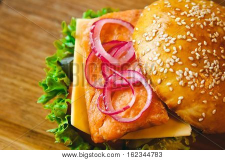 fish Burger with salmon on a wooden background tray