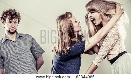 Aggressive mad women fighting over man pulling hair. Young jealous girls wooing guy. Violence.