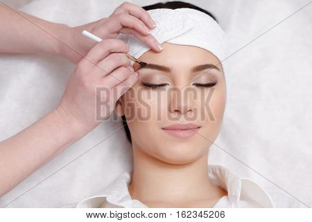 Permanent makeup. Permanent make-up wizard makes eyebrow correction procedure. Beautiful young woman gets eyebrow correction procedure. Young woman tweezing her eyebrows in beauty saloon