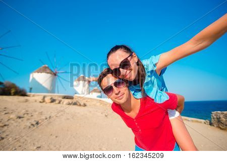 Family taking selfie with a stick in front of windmills at popular tourist area on Mykonos island, Greece