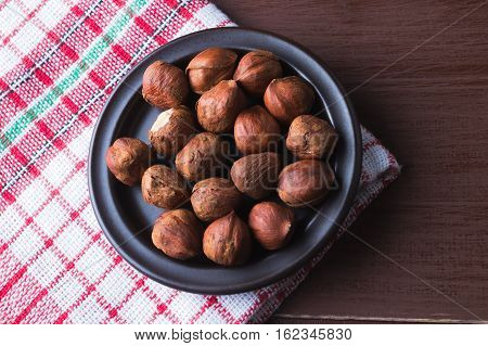 Hazelnuts on a plate with old kitchen dishcloth. Brown natural table. Flat lay top view. Vegetarian food concept.