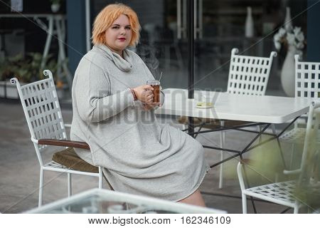 Cheerful lady is sitting at the table in cafe and drinking tea.