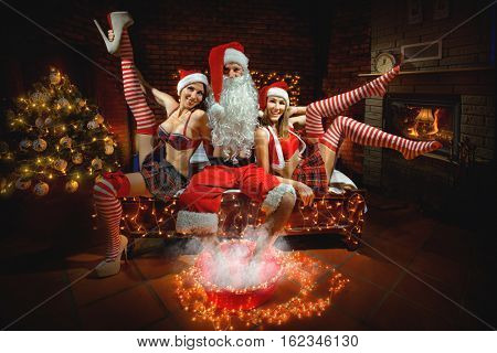 Portrait of Santa Claus sitting on the bed and steaming his legs around two sexy girls in Santa hats