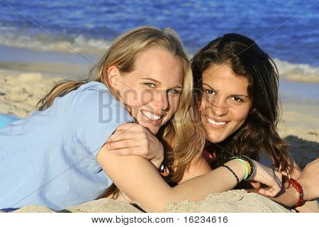 2 smiley friends relax on beach
