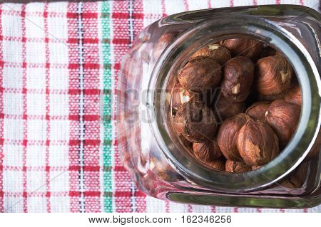Hazelnuts in a jar with old kitchen dishcloth. Flat lay top view. Copy space on the left. Vegetarian food concept.