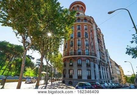 Streets scenes of Madrid.  View from corner of Alfonso XII and Velasco Streets.  European architecture shown in a rounded corner building.  Cars parked on the side of Velasco Street in Madrid.  Unusually warm November day in one of the main parks of the c
