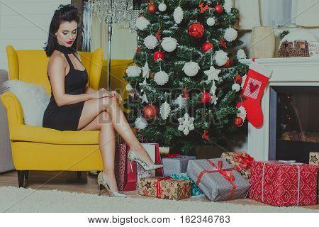 Sexy woman posing in sexy dress near the xmas tree