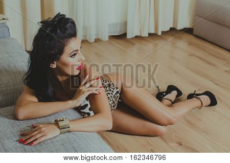 Beautifu woman posing on parquet in the living room