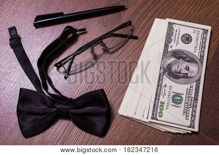 glasses black bowtie black pen note book page and money a place for records business plan money background hundred dollar bills front side. background of dollars new hundred-dollar bil face the evolution of the bill in one hundred dollars copyspace