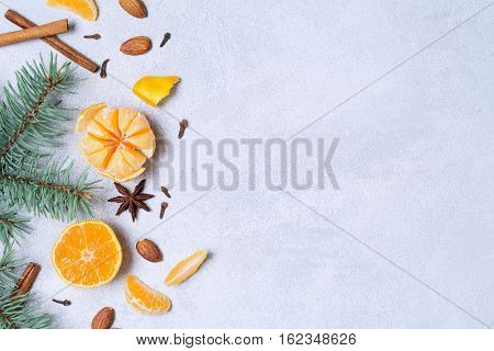 Winter flat lay composition with tangerines, spices, almonds and fir tree on blue background. Top view, copy space for text