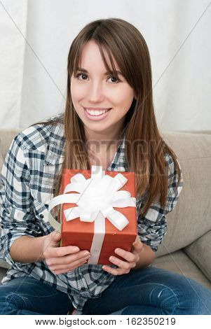 Portrait of happy young woman with xmas present sitting on sofa at home. Beautiful brunette woman holding christmas present