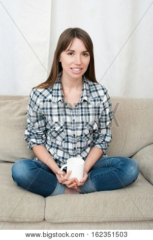 Portrait of young woman sitting on couch in her living room and drinking coffee or tea. Attractive woman drinking coffee indoor and smiling