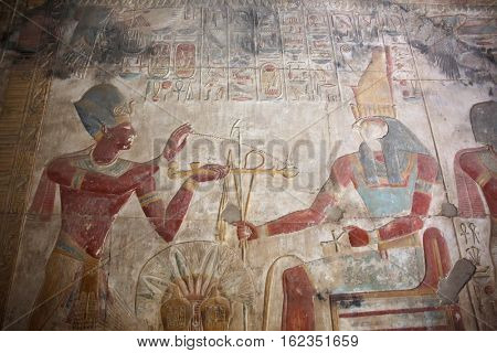 MORTUARY TEMPLE OF SETI I, ABYDOS, EGYPT - NOVEMBER 12, 2016:  Ancient Egyptian engravings: Seti wearing a blue crown burning incense over an offering
