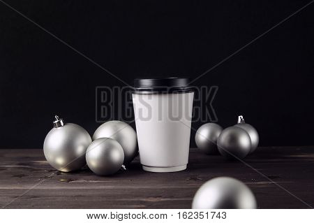Paper coffee cup and christmas ball on a wooden table. Holiday toys. Silver balls on the background. Happy new year. Hipster cafe. Template for design